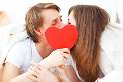 Lover couple kissing with a red heart in bed. Concept for Valentine's Day. lover couple kissing with a red heart in bed Royalty Free Stock Photo