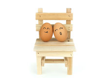 Lover eggs couple, lean on each other on wooden chair, isolated on white background Royalty Free Stock Photography