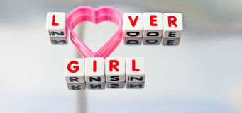 Lover girl. Text 'lover girl' in uppercase red letters inscribed on small white cubes with  letter 'o' replaced by a pink heart shape, silver background Stock Photography