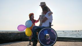 Lover handicapped in wheel chair with lucky Family child consider belly of pregnant mom vacation. On sea together stock video footage