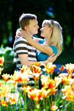 Lover man and girl among red yellow flowers. In spring park Royalty Free Stock Photo