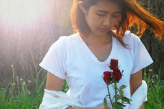 Lover moment. Asian young woman are moment in love. She sit on the field in the evening sunshine have a mild breeze and holding a red rose in hand Royalty Free Stock Images