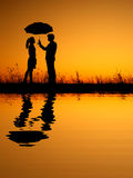 In lover Reflection of Man and woman holding umbrella in evening sunset silhouette Royalty Free Stock Photos