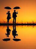 In lover Reflection of Man and woman holding umbrella in evening sunset silhouette Stock Photography