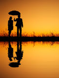 In lover Reflection of Man and woman holding umbrella in evening sunset silhouette Stock Photo