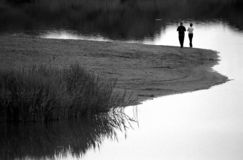 Lovers. Walking along the shore of a lake stock photo