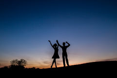 Lovers admire the beautiful sky and waving their hands. Relax in nature. Camping. A couple enjoying the sunset Royalty Free Stock Images