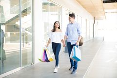Lovers With Bags Spending Weekend Shopping In Mall. Teenage lovers with bags spending weekend shopping in mall Royalty Free Stock Photography