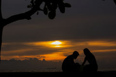 Lovers by the Bay. Enjoying the beauty of setting the Sun Royalty Free Stock Photos
