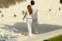 Lovers at the beach. Young couple holding hands and walking along the beach stock images