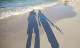 Lovers on the beach walking. Royalty Free Stock Photos