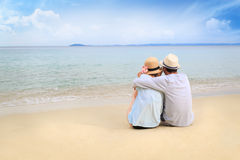 Lovers on the beach. Young couple enjoying their time on the beach. Snuggled togehter Royalty Free Stock Images