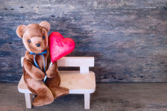 Lovers bear and red chocolate heart. Stock Photos