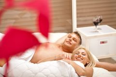 Lovers in bed smiling to camera Stock Photo