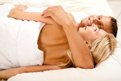 Lovers in bedroom smiling Stock Photo