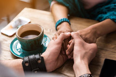 Lovers bonding arms together in cafe. Close up of affectionate couple holding hands with gentleness. They are sitting at table near cup of coffee Royalty Free Stock Photography