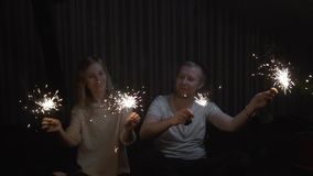 Lovers boy and girl with sparklers in hands having fun and kissing. slow motion stock footage