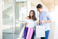 Lovers Carrying Multicolored Paperbags While Spending Time Toget. Smiling teenage lovers carrying multicolored paperbags while spending time together in shopping Stock Photography