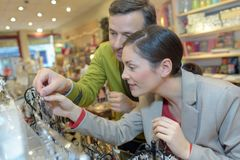 Lovers choosing jewellery at mall. Lovers choosing jewellery at the mall Royalty Free Stock Photos
