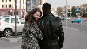 Lovers in the city. Beautiful girl looks back in camera, leans on her mans shoulder. Back view, slow mo, steadicam shot. Happy lovers walking in the city stock video footage