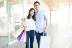 Lovers With Colorful Shopping Bags On Corridor In Mall. Smiling teenage lovers with colorful shopping bags on corridor in mall Stock Photography