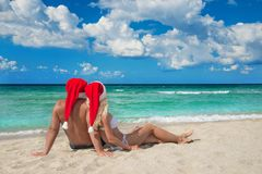 Lovers couple in red santa hats relaxing at sandy beach Stock Images