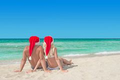 Lovers couple in red santa hats relaxing at tropical sandy beach Stock Image