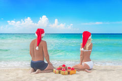 Lovers couple in santa hats and many golden packed presents on s Royalty Free Stock Photo