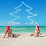 Lovers couple in santa hats at tropical sandy beac Stock Photography