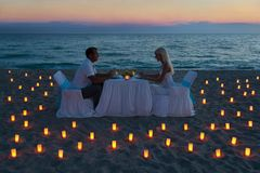 Lovers couple share a romantic dinner on sea beach Stock Photos