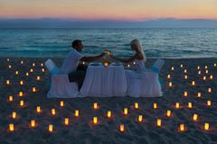 Lovers couple share a romantic dinner on sea beach. Lovers couple share a romantic dinner with candles on sandy sea beach during sunset royalty free stock images