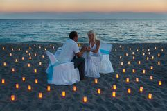 Lovers couple share a romantic dinner on sea beach Royalty Free Stock Image
