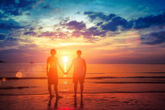 Lovers couple standing hand in hand on the beach during sunset. Stock Images
