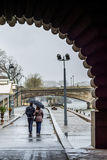 Lovers couple walking on the Sein quai in Paris during a rainy day Royalty Free Stock Image