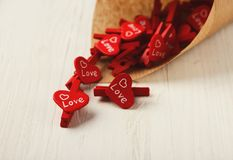 Lovers day background with red clothespins in craft cornet. Valentine day background with heartshaped clothespins scattering out from craft paper cornet on white Royalty Free Stock Photos