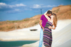 Lovers in desert near oasis. Tender lovers on romantic travel honeymoon vacation summer holidays romance. Young happy couple on the beach with white sand Royalty Free Stock Photos
