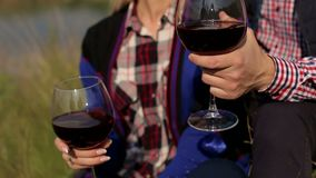 Lovers drink wine on the riverbank, close-up. Lovers drink wine on the riverbank. Couple in love drinking wine on the shore of a large lake, close-up stock video footage