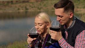 Lovers drink wine on the riverbank. Couple in love drinking wine on the shore of a large lake, close-up stock video