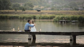 Lovers drinking champagne on the lake. HD stock footage