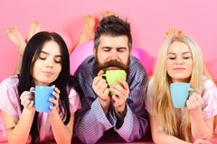 Lovers drinking coffee in bed. Threesome relax in morning with coffee. Stormy night concept. Man and women in domestic. Clothes, pajamas. Man and women, friends stock image
