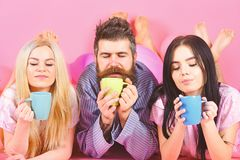 Lovers drinking coffee in bed. Threesome relax in morning with coffee. Stormy night concept. Man and women in domestic. Clothes, pajamas. Man and women, friends stock photo