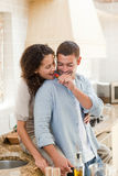 Lovers eating a strawberry in their kitchen Stock Image