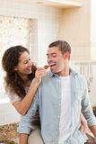 Lovers eating a strawberry in their kitchen Royalty Free Stock Photography