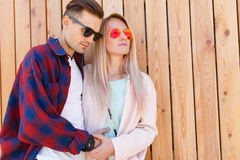 Lovers embrace on fence background. Young lovers embrace on wooden fence background Royalty Free Stock Image