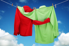 Lovers embrace. Laundry hanging on a clothesline concept for love and romace with two shirts embracing each other looking at a blue sky Stock Photo