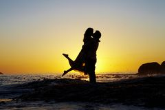 Lovers embrace silhouetted by a sunset stock photography