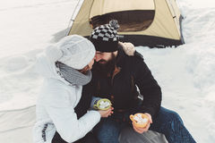 Lovers embrace during a winter hike. Young passionate couple sitting in the snow against the backdrop of a tourist tent and holding a marshmallow for a barbecue Royalty Free Stock Images