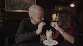 Lovers enjoying each other`s company in a cafe and drinking coffee from one cup. stock video footage
