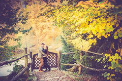 Lovers in fall. Two lovers embracing near wooden fence with gates, fall or autumn background royalty free stock photos
