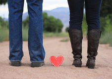 Lovers Feet. Man and woman's feet with heart between them Stock Photography